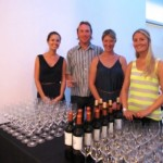 Volunteer staff (Ms. Sarah, Mr. Andre, Ms. Mia and Ms. Lauren) smiling and ready to serve fine wines from the West Indies Wine Company.