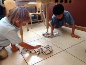 Two students work together to wipe a spill in the kitchen area.